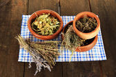 Medicinal Herbs in wooden bowls on napkin on wooden table — Foto de Stock