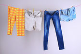 Laundry line with clothes on wall background — Stock Photo