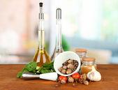 Composición del mortero, botellas con aceite de oliva y vinagre y hierbas verdes, sobre fondo brillante — Foto de Stock