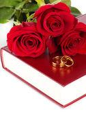 Trauringe mit rosen auf bibel isoliert auf weiss — Stockfoto