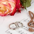 Treble clef, roses and wedding rings on musical background — Stock Photo