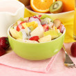 Useful fruit salad of fresh fruits and berries in bowl on napkin on wooden table close-up — Stock Photo #26604375