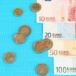 Euro banknotes and euro cents on blue background — Stock Photo #26607621