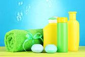 Kosmetyki dla dzieci, ręcznik i mydło na drewnianym stole, na niebieskim tle — Zdjęcie stockowe