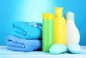 Bebek kozmetik, havlu ve sabun mavi zemin üzerine ahşap tablo — Stok fotoğraf