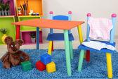 Малые и красочные стол и стулья с baby одежда — Стоковое фото