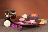 Spa composition with aroma oils on brown background — Stock Photo