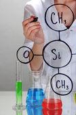 химик женщина, написание формул на стекле на сером фоне — Стоковое фото