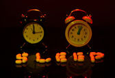 Old style alarm clocks and pills, on dark background — Stock Photo