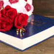 Wedding rings on bible with roses on wooden background — Stock Photo #26682759