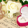 Stock Photo: Treble clef, roses and box holding wedding ring on musical background