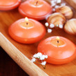 Photo: Beautiful candles in water on wooden table close-up