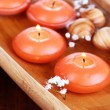 Beautiful candles in water on wooden table close-up — Photo #26683609