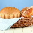 Composition with bread and rolls on wooden table, on color background — Stock Photo #26684585