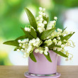 Beautiful lily of the valley in vase on nature background — Stock Photo