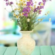 Bouquet of wild flowers in vase, on bright background — Stock Photo
