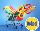 Trolley with school equipment on blue background — Stock Photo