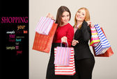 Two girl friends with shopping on grey background — Stock Photo