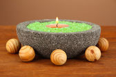 Candle in stone bowl with marine salt, on wooden table, on brown background — Stock Photo