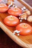 Beautiful candles in water on wooden table close-up — Stok fotoğraf