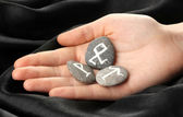 Fortune telling with symbols on stone in hand on black fabric background — Stock Photo