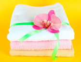 Towels tied with ribbon on yellow background — Stock Photo