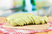 Fresh marrows on cutting board, on wooden table, on bright background — Stock Photo