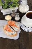 魚のサンドイッチとまな板木製テーブルの上にお茶のカップ — ストック写真
