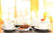 Cups of coffee and cookies on napkin on dark table on room background — Stock Photo