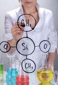 Chemiker frau schreiben von formeln auf glas auf grauen hintergrund — Stockfoto