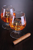 Brandy glasses with ice on wooden background — Stock Photo