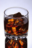 Brandy glass with ice on grey background — Stock Photo
