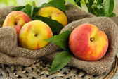 Ripe sweet peaches on wooden table in garden, close up — Stock Photo