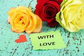 木製の背景の色で、美しいバラの花 — ストック写真