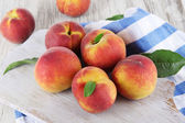 Peaches on board on napkin on table on wooden background — Stock Photo