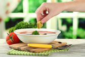 Bowl of soup with bouillon cube on wooden table — Stock Photo