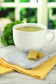 Cup of soup with bouillon cubes on wooden table — Stock Photo