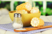Boiled corn in bowl, on wooden table, on bright background — Stock Photo