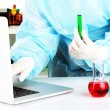 Scientist entering data on laptop computer with test tube close up — Stock Photo #26719915