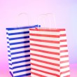 Stripped bags on light pink background — Stock Photo #26719547