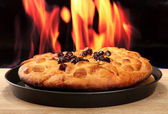 Tasty homemade pie with jam, on wooden table on flame background — Stock Photo