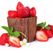 Ripe sweet strawberries with leaves in wooden vase, isolated on white — Stock Photo