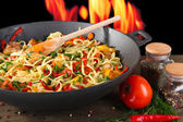 Noodles with vegetables on wok on fire background — Stock Photo