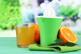 Citrus press, glass of juice and ripe oranges on green wooden table — Stock Photo
