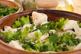 Boiled meat on wooden bowl and herbs on wooden table close-up — Stock Photo