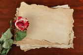 Old paper and rose on wooden background — Stock Photo