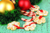 Christmas cookies and decorations on color wooden background — Stock Photo