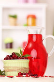 Pitcher of cranberry juice and red cranberries on table — Stock Photo