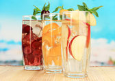 Glasses of fruit drinks with ice cubes on blue background — Stock Photo