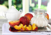 Peaches with sugar on metal tray on napkin on table on window background — Stock Photo